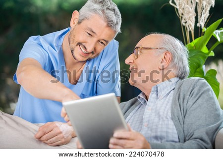 Smiling male nurse assisting senior man in using tablet PC at nursing home porch - stock photo