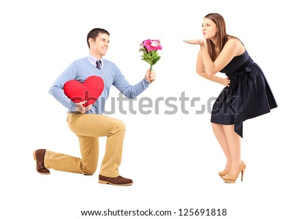 Smiling male on knee giving a red heart and flowers to a woman blowing him a kiss isolated on white background - stock photo