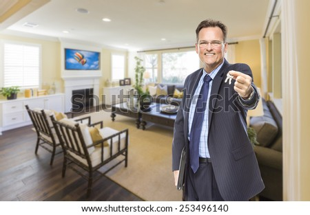 Smiling Male Real Estate Agent Handing Over Keys Standing in Beautiful Living Room. - stock photo