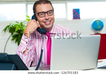 Smiling male representative engaged over a business call with laptop in front of him.