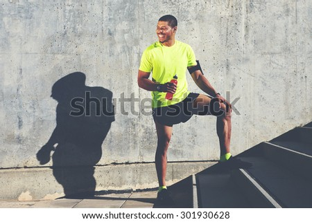 Smiling male runner in bright t-shirt holding bottle of energy drink while standing against cement wall background with copy space area for your advertising, happy afro american athlete having a rest  - stock photo