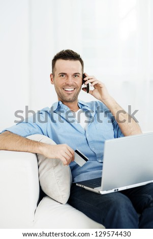 Smiling male shopping via internet - stock photo
