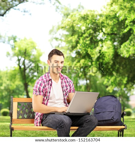 Smiling male student sitting on a bench and working on a notebook computer in park, shot with a tilt and shift lens