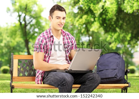 Smiling male student sitting on a wooden bench and working on a laptop in park