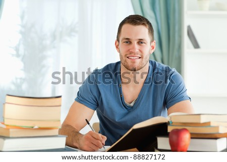Smiling male student working on his book report