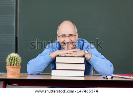 Smiling male teacher with a stack of books in front of the blackboard in the schoolroom - stock photo