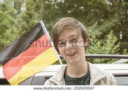 smiling male teenager in front of a german flag.