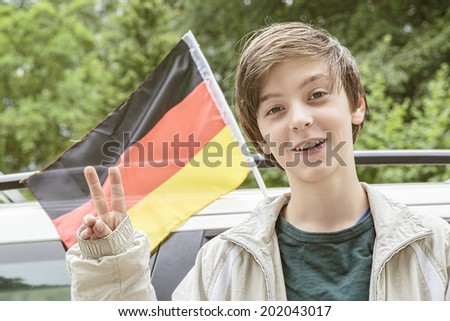 smiling male teenager showing the victory gesture in front of a german flag.