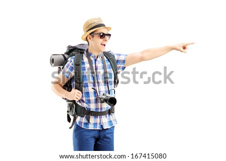Smiling male tourist with backpack pointing with his finger isolated on white background