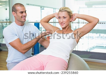 Smiling male trainer assisting woman with abdominal crunches at the gym - stock photo