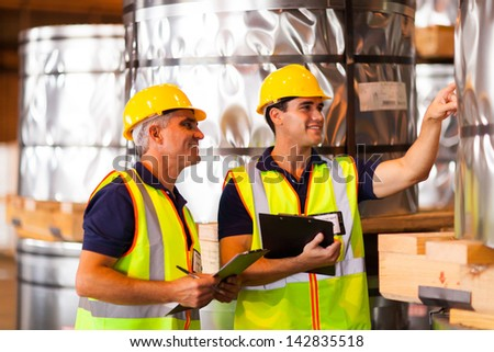 smiling male warehouse workers counting stock - stock photo