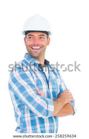 Smiling male worker wearing hardhat while standing arms crossed on white background - stock photo