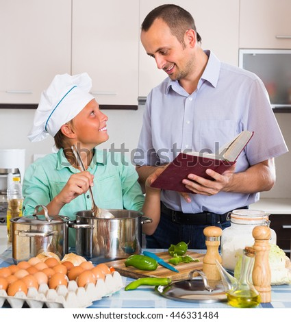 Smiling man and his cheerful teenage son cooking dinner together at kitchen