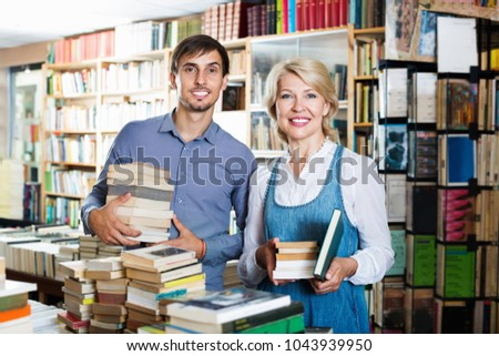 Smiling  man and positive glad mature woman holding books in hands in book store