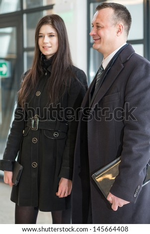 Smiling man and woman in a coat stand near the glass door with notebooks