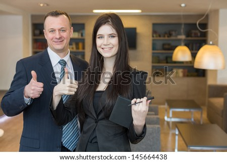 Smiling man and woman in business suits standing and doing a thumbs up, focus on a girl.