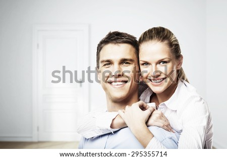 smiling man and woman in white room - stock photo