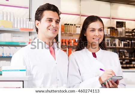 Smiling man and woman pharmacist with a notebook in the hands at the chemists shop