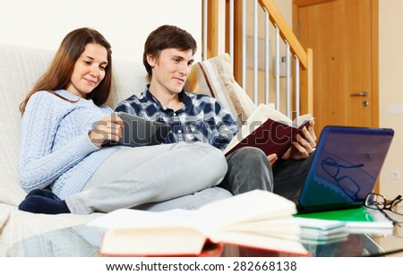 Smiling man and woman preparing for exams at home