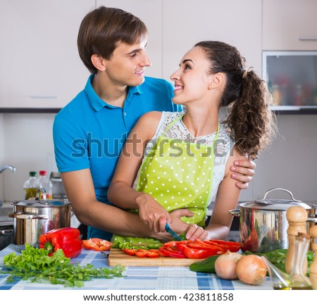 smiling man and woman standing near table with vegetables