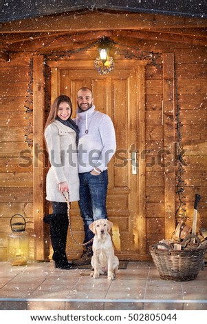 Smiling man and woman with dog in front of wooden cottage