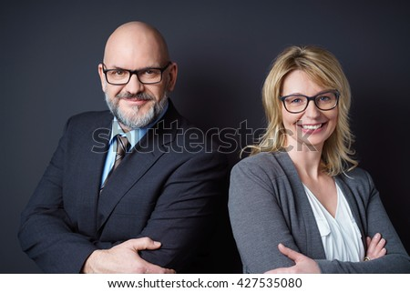 Smiling man and women in business attire each wearing glasses and both with their arms crossed - stock photo