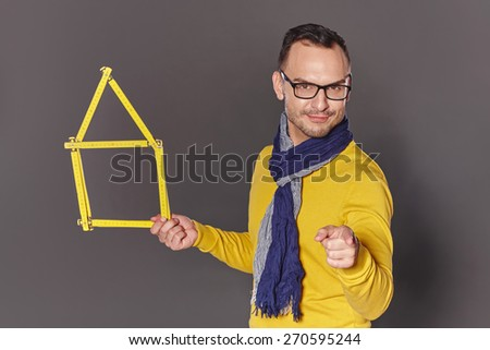 Smiling man architect designer showing house home concept and pointing at camera - stock photo