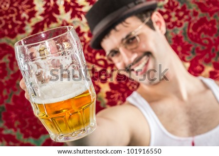 Smiling man at retro vintage bar with mostly empty mug of yellow beer toasting you, breaking fourth wall, in glasses hat and mustache, wife beater - stock photo