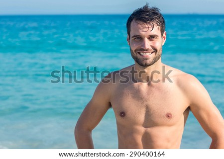 Smiling man at the beach looking at camera on a sunny day