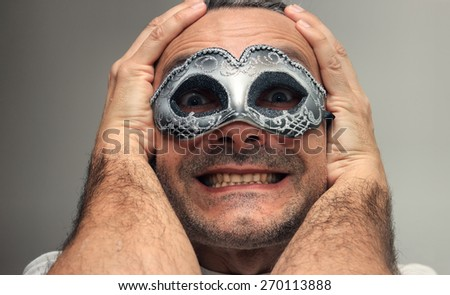 smiling man at the masquerade with silver mask - stock photo