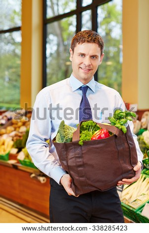 Smiling man buying fresh vegetables in a supermarket