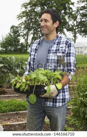 Smiling man carrying plants in the field