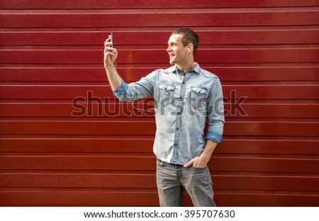 Smiling man casual dressed standing against red background, talking at cellphone - stock photo