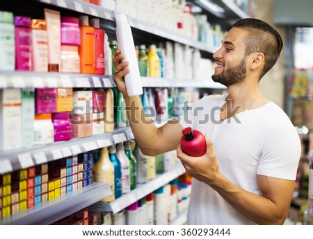 Smiling man chooses shampoo in supermarket - stock photo
