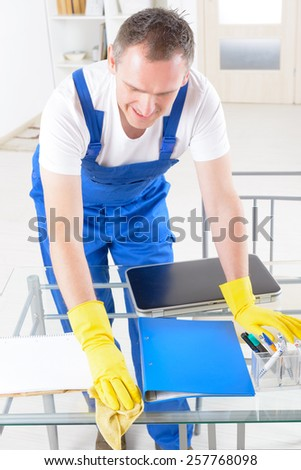 Smiling man cleaner wearing yellow gloves - stock photo
