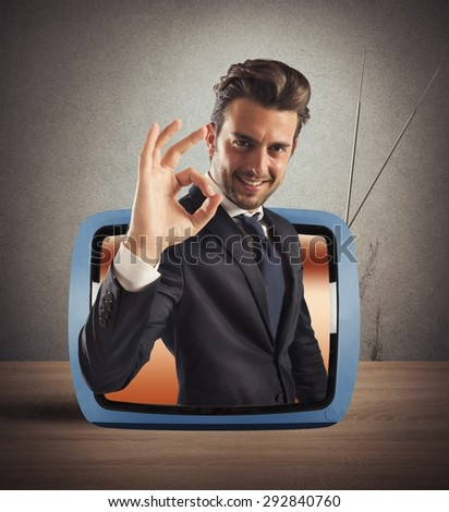 Smiling man comes out of vintage TV - stock photo