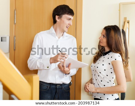 Smiling man conducting  survey among people at door