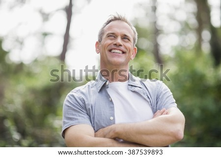 Smiling man crossing his arms outside