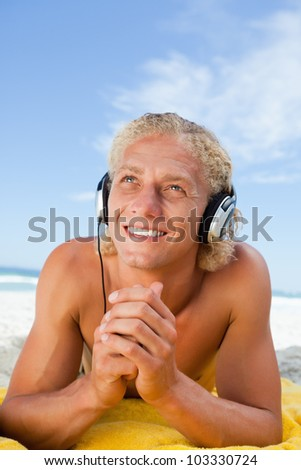 Smiling man crossing his hands while listening to music with his headset - stock photo