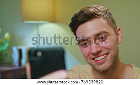 Smiling Man Drinking Coffee and Using Cellphone in Home