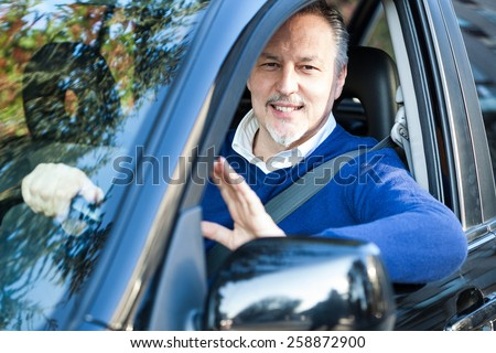 Smiling man driving his car - stock photo