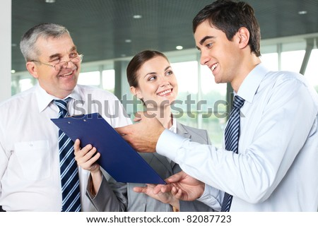 Smiling man explaining business document while his partners looking at him - stock photo