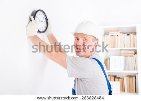 Smiling man hanging wall clock wearing protective helmet - stock photo