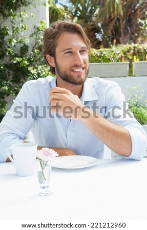 Smiling man having a coffee outside at the coffee shop - stock photo