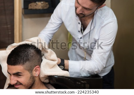 Smiling Man Having His Hair Washed At Hairdresser's - Hairstylist Hairdresser Washing Customer Hair - Young Man Relaxing In Hairdressing Beauty Salon - stock photo