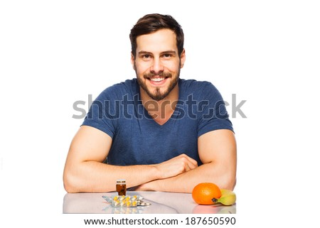 smiling man having in front fruits and pills - stock photo