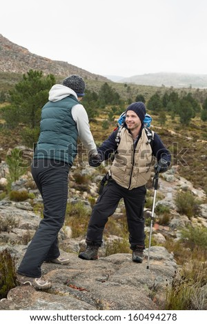 Smiling man helping a woman to get down a rock on a hike