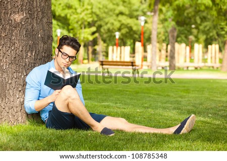smiling man holding a book on the grass in the park - stock photo