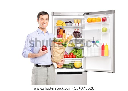Smiling man holding a paper bag in front of refrigerator full of products and looking at camera, isolated on white background - stock photo