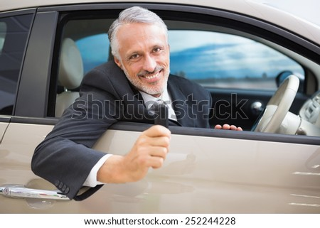 Smiling man holding car keys while sitting on a car at new car showroom - stock photo